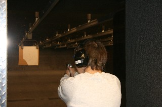 A color photograph showing a student shooting at the indoor range.